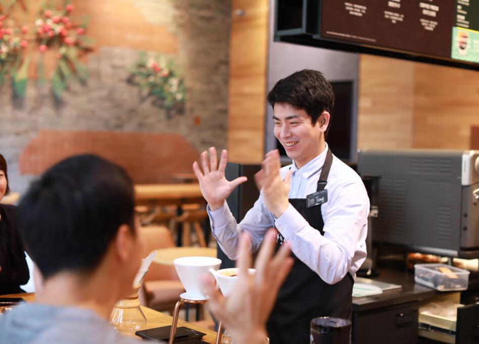 Starbucks employee communicating in Sign Language