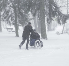 Old man slowly and hard pushing woman in wheelchair in winter day. Heavy snow storm in tree park.