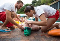 Rescue workers helping unconscious man at poolside