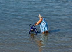 Elderly lady walks with walker in the sea
