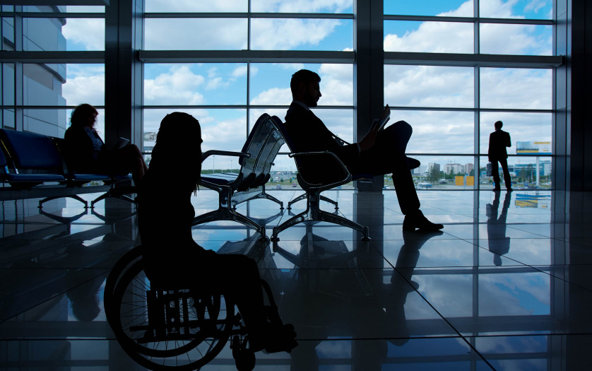woman in wheelchair and passengers are waiting at the airport