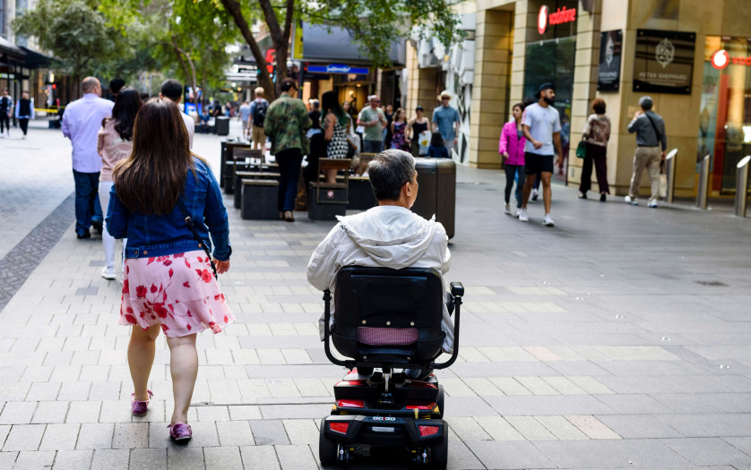 A disabled man on mobility scooter and other people at Sydney CBD