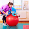 cute kid with disability has musculoskeletal therapy by doing exercises in body fixing belts on fit ball