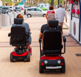 elderly Couple ride along the sidewalk to an electric wheelchair.
