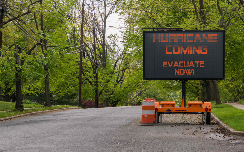 Hurricane Coming Evacuate Now warning information sign on trailer with LED face on suburban street lined with trees