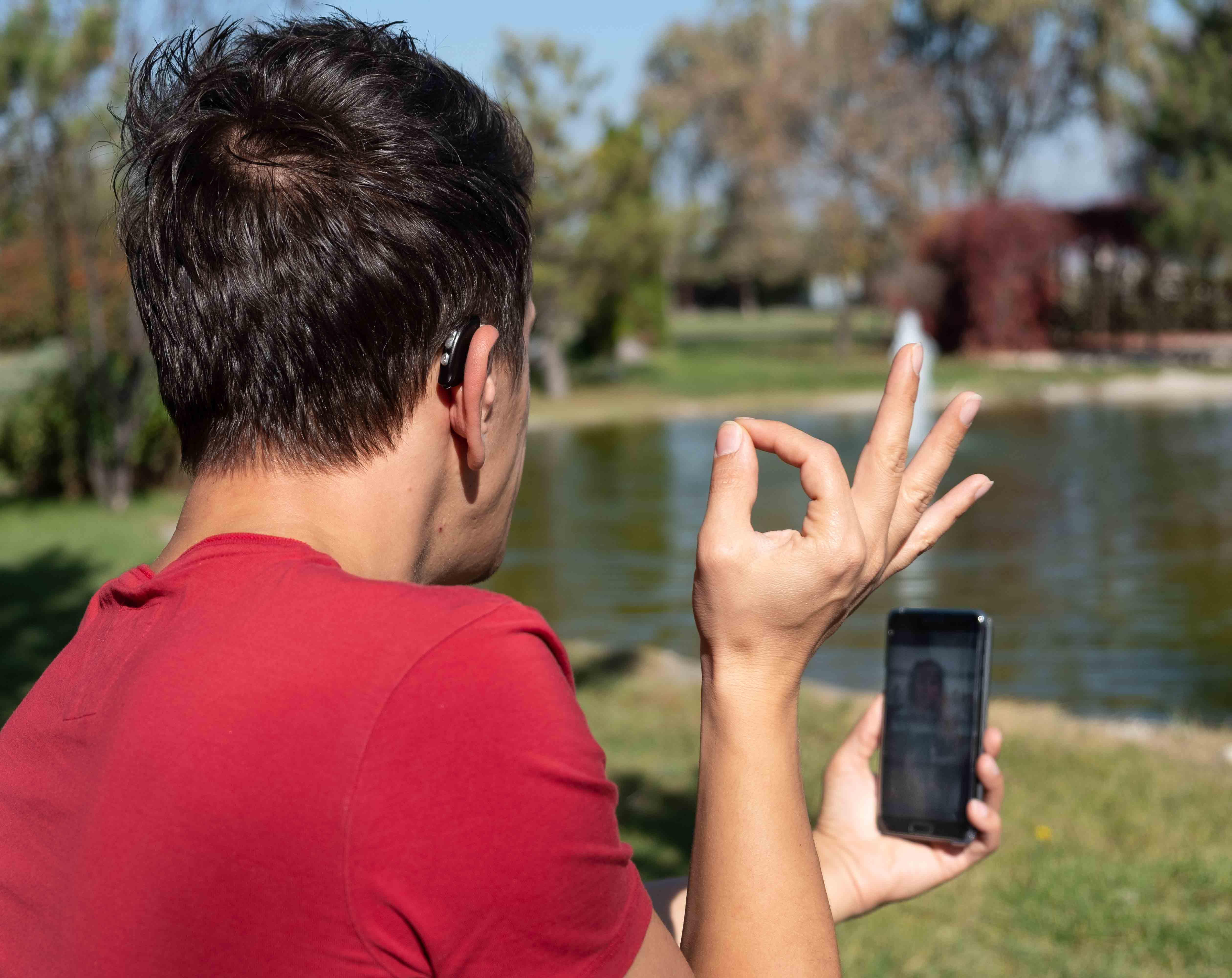man communicating with sign language at smartphone