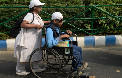 woman helps a disabled person in wheelchair in India