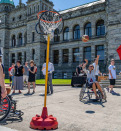 wheelchair user playing basket ball in the street