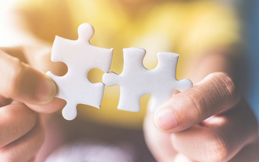 Hand connecting jigsaw puzzle