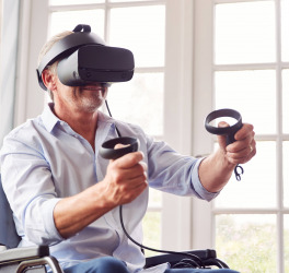 a man in wheelchair doing exercise using VR headset