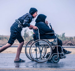son pushing mother in wheelchair