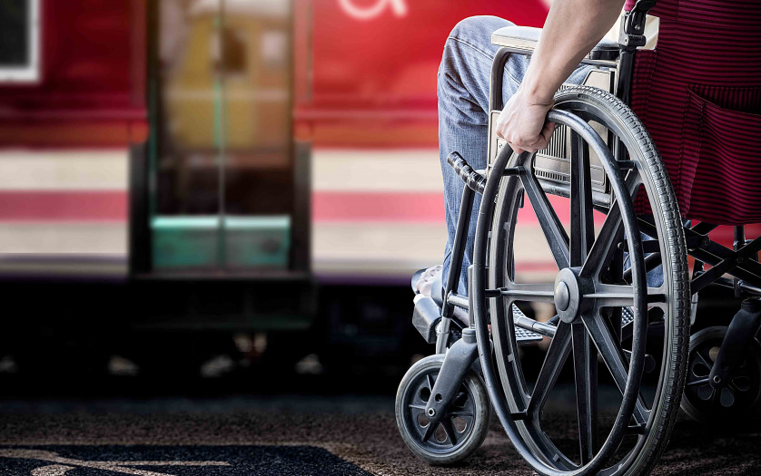 man in his wheelchair at railway station platform waiting for train