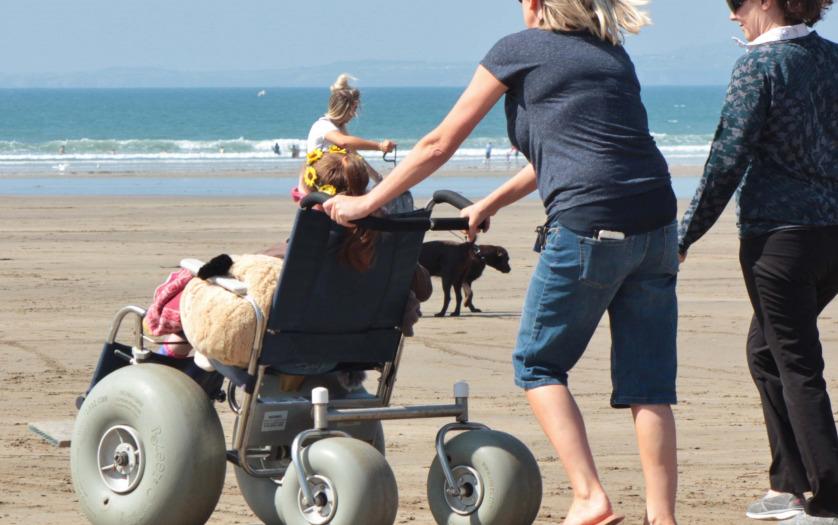 Woman pushing beach wheelchair