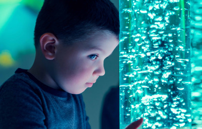Child in sensory stimulating room, interacting with colored lights bubble tube lamp