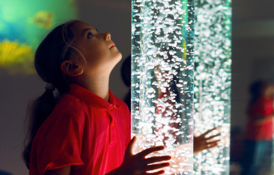 Child interacting with colored lights bubble tube lamp