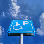 Low angle view of blue handicapped parking sign against blue cloudy sky at day time
