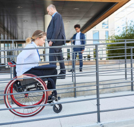 Woman in a wheelchair on a ramp in front of the office