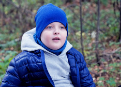 child autistic in blue hat and blue jacket playing with wilted leaves in autumn Park