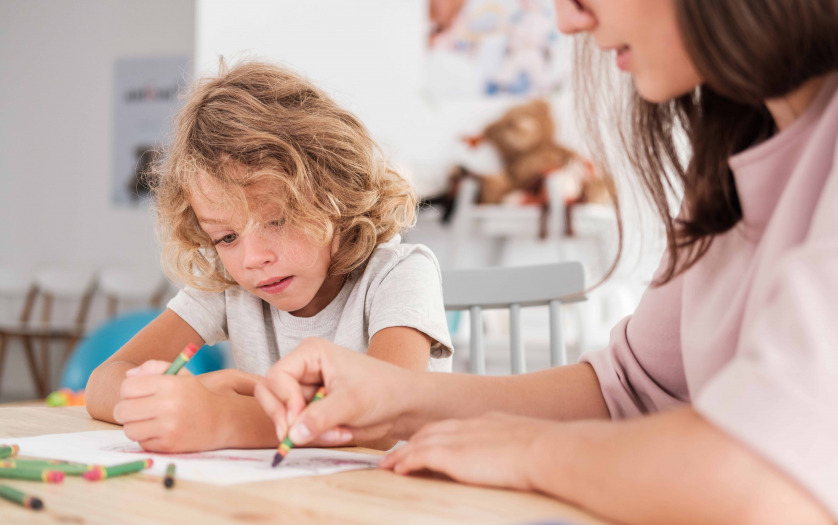Close-up of a child with autism and teacher by a table drawing with crayons