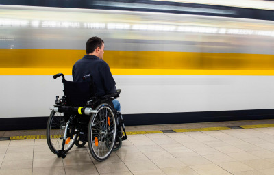 Back view of man in his electric wheelchair at underground platform waiting for train with motion blur of passing train in the background