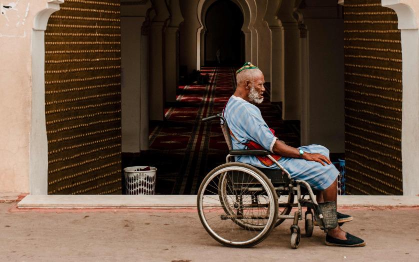 Muslim man in wheelchair at the door of the mosque.
