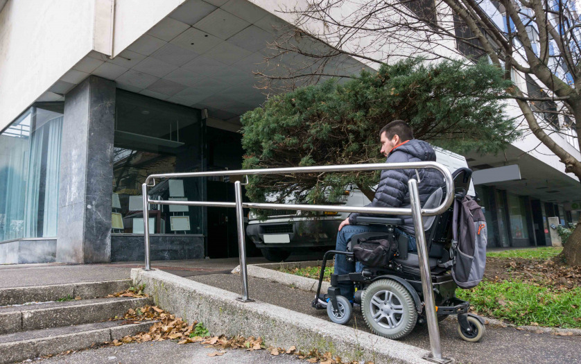 Man in a wheelchair using a ramp next to stairs.