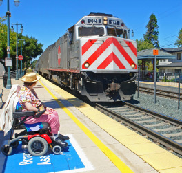 A disabled woman ready for boarding watches her Caltrain passenger train arrive.