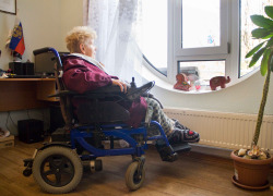 A woman in wheelchair looks out the window.