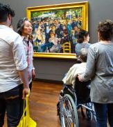 Visitors in art museum Orsay (Musee d'Orsay). Elderly man is sitting in wheelchair looking at artwork of impressionist artist Renoir.