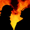 A striking silhouette image of two firemen called to an Australian bushfire blaze that started at night time. The men are discussing their plans for controlling the blazing flames.