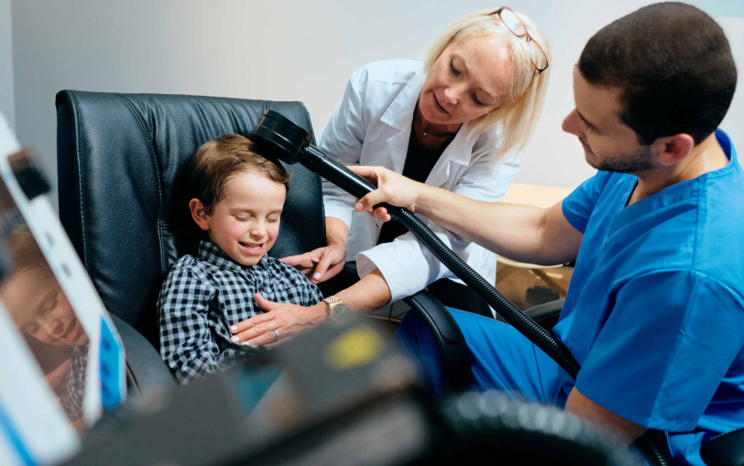 Paediatrician Doctor Doing Brain Treatment To Autistic Child In Clinic