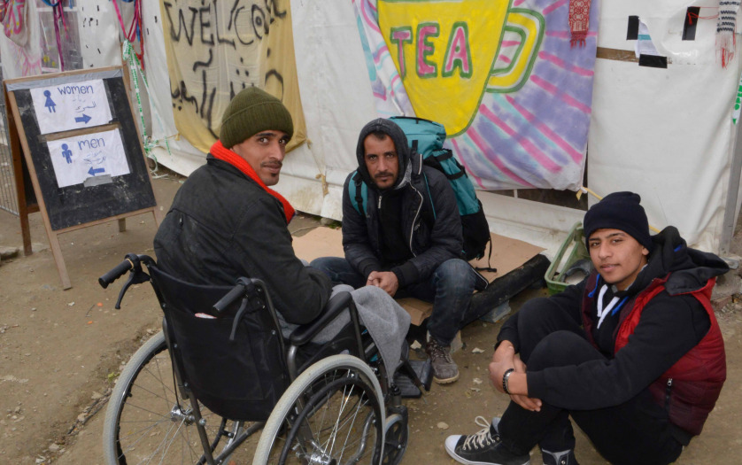 man in wheelchair with other refugees