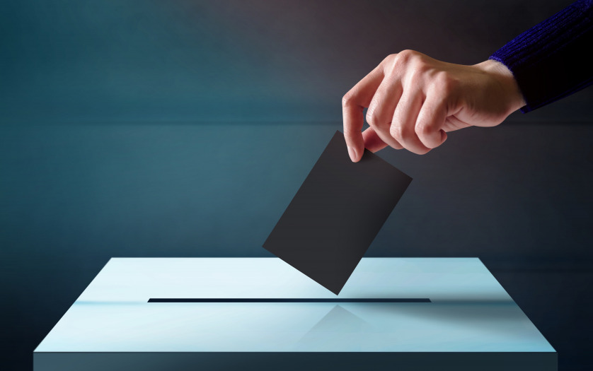 Hand dropping a ballot card into the vote box