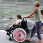 Disabled child in a wheelchair on a city street