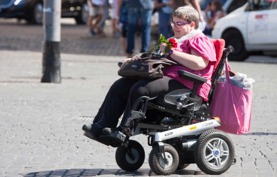 A woman with a disability through the city with his means of transport. She keeps some roses in her hand.
