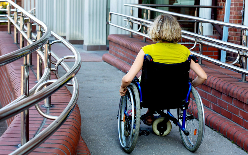 adult woman on wheelchair entering the building