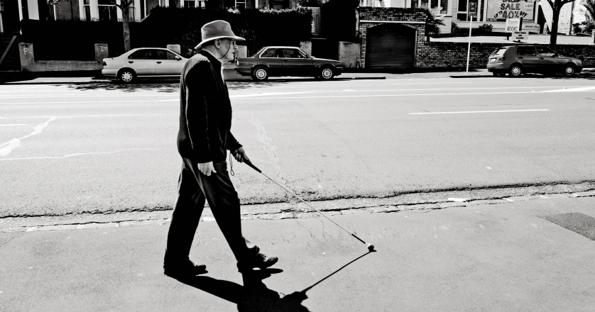 Blind man walks with a cane in Auckland street