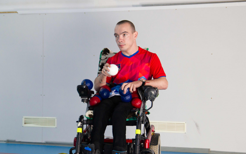 A disabled man in a wheelchair. Holding a white little ball.