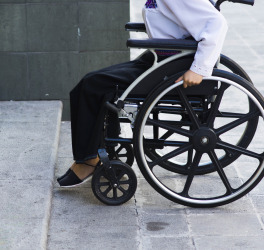 woman in wheelchair in front of inaccessible building