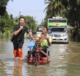 A volunteers help disable man with his wheel chair walk through flood and he still smile in Southern, Thailand.