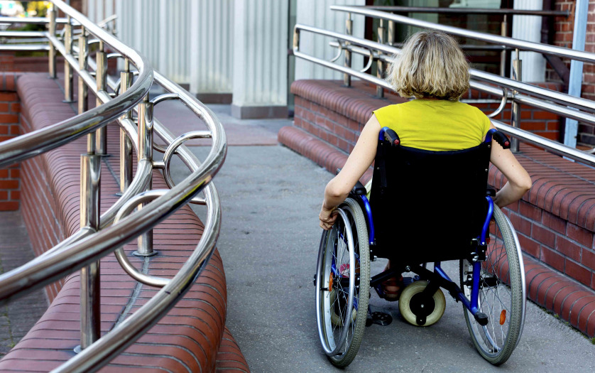 woman in wheelchair entering the building