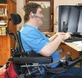 a man in wheelchair using computer
