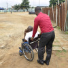 View of a person promoting the integration and displacement of a person in wheelchair in order to ease his travel