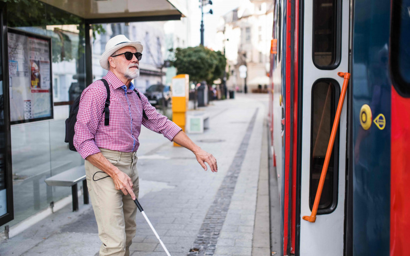 A senior blind man with white cane getting on public transport in city.