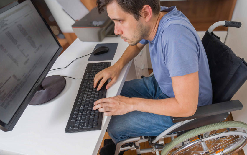 man in wheelchair is working with computer in office.