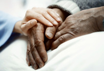 Hand of woman touching senior man in hospital
