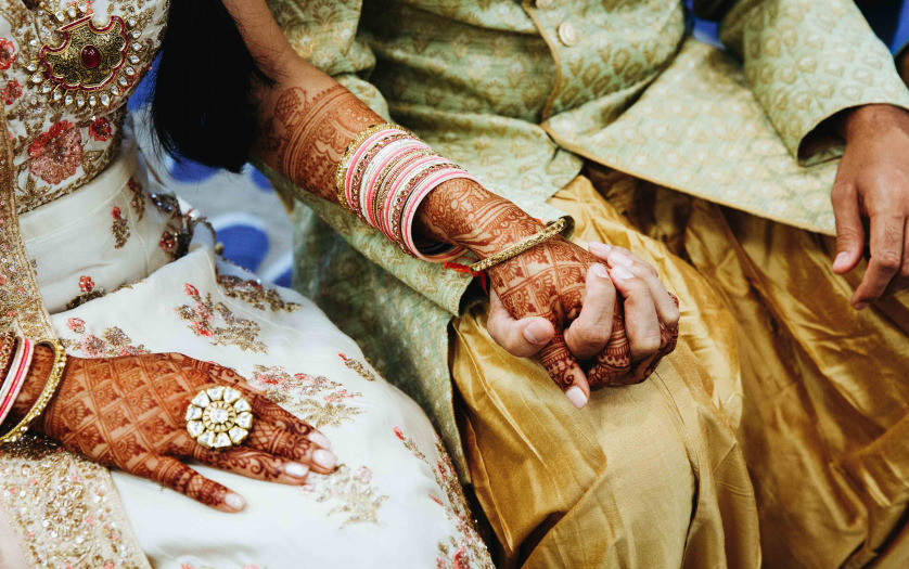 Indian wedding couple are holding hands