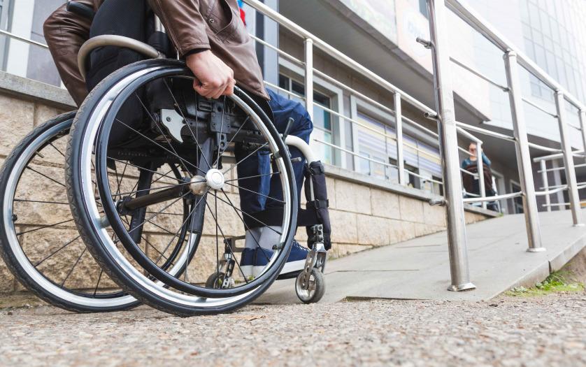Man in a wheelchair use a wheelchair ramp.