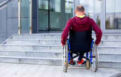 man in wheelchair in front of stairs