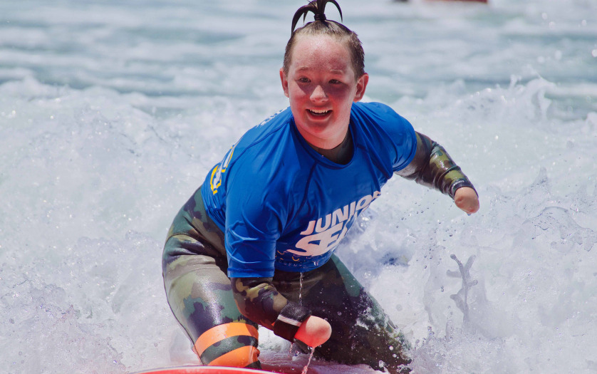 Surfer girl with disability having a blast on the waves at Beach